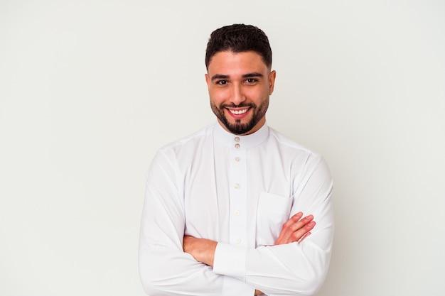 Giovane uomo arabo che indossa abiti tipici arabi isolati su bianco che si sente fiducioso, incrociando le braccia con determinazione.