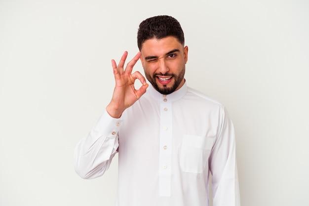 Il giovane arabo che indossa abiti tipici arabi isolati su bianco strizza l'occhio e tiene un gesto giusto con la mano.