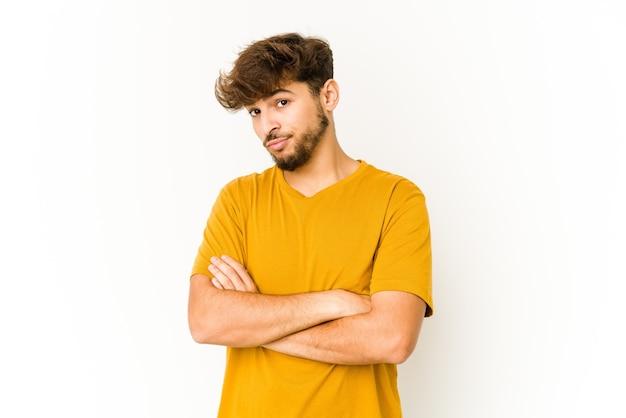 Giovane uomo arabo sul muro bianco, infelice guardando con espressione sarcastica.