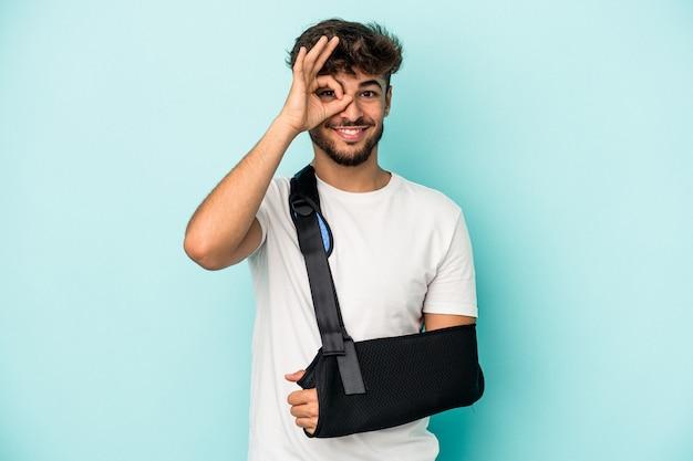 Il giovane uomo arabo con la mano rotta isolata su fondo blu ha eccitato mantenendo il gesto giusto sull'occhio.