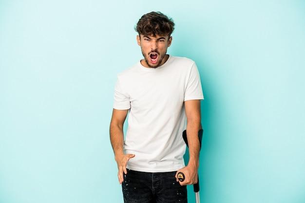 Giovane uomo arabo con le stampelle isolato su sfondo blu che urla molto arrabbiato e aggressivo.