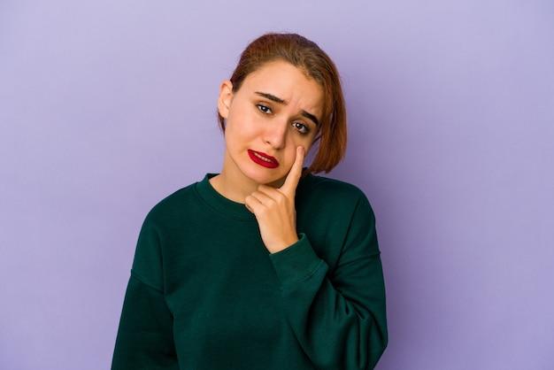 Giovane donna araba di razza mista che piange, insoddisfatta di qualcosa, agonia e concetto di confusione.