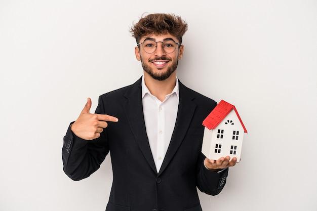 Giovane uomo arabo immobiliare che tiene una casa modello isolata su sfondo isolato persona che punta a mano a uno spazio copia camicia, orgoglioso e fiducioso