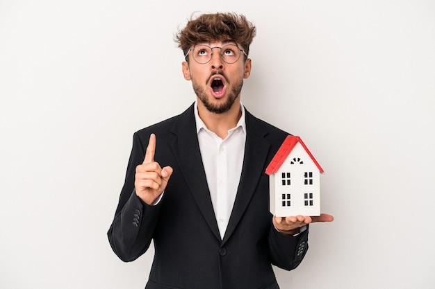 Giovane arabo immobiliare uomo in possesso di un modello di casa isolata su sfondo isolato rivolto verso l'alto con la bocca aperta.