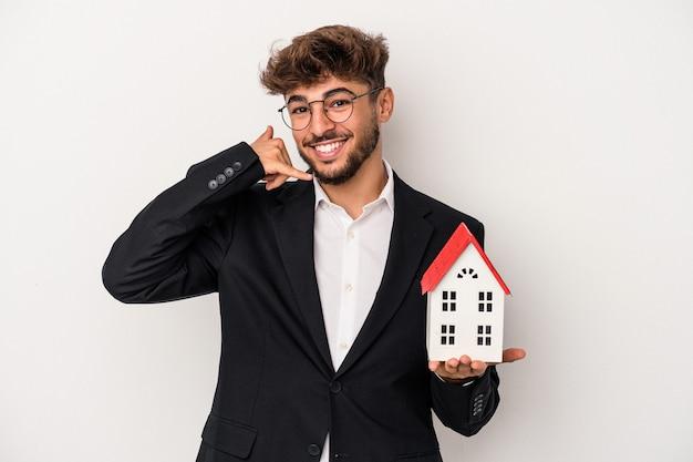 Giovane uomo arabo del bene immobile che tiene una casa modello isolata su fondo isolato che mostra un gesto di chiamata del telefono cellulare con le dita.