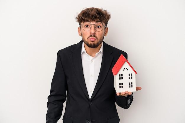 Il giovane uomo arabo del bene immobile che tiene una casa di modello isolata su fondo isolato alza le spalle e apre gli occhi confusi.