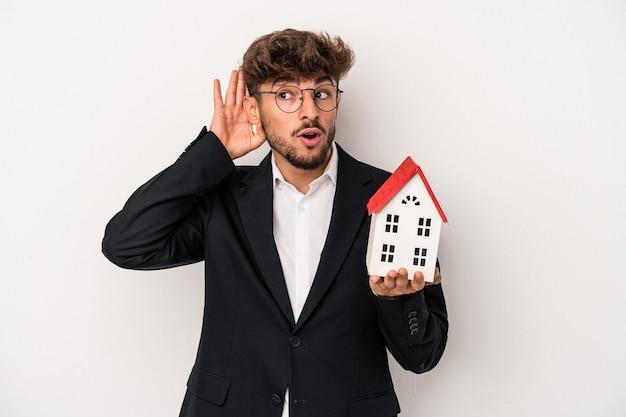 Giovane uomo arabo immobiliare che tiene una casa modello isolata su sfondo isolato cercando di ascoltare un pettegolezzo.