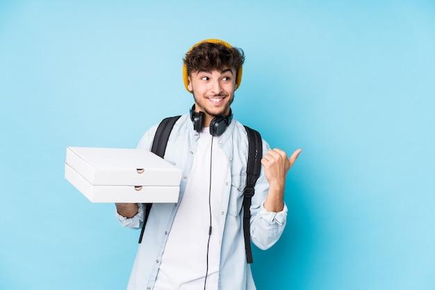 Uomo giovane studente arabo che tiene pizze isolati punti con il pollice lontano, ridendo e spensierato.