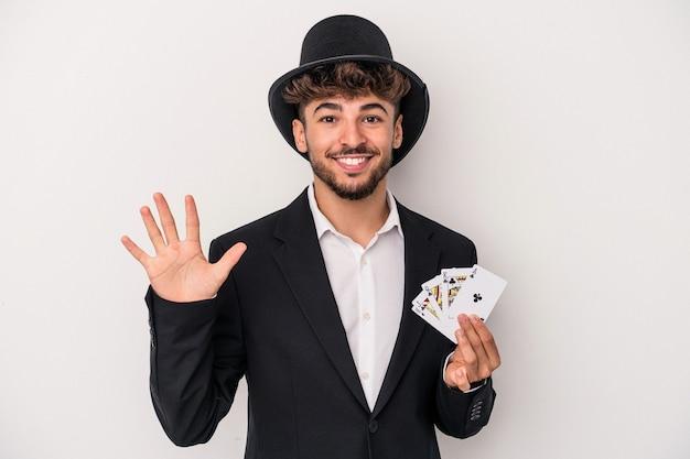 Giovane uomo arabo del mago che tiene le carte magiche isolate su fondo bianco sorridente allegro che mostra il numero cinque con le dita.