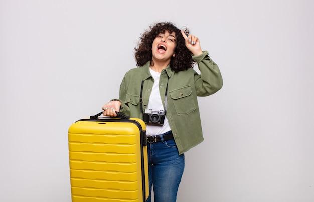 Giovane donna araba che si sente come un genio felice ed eccitato dopo aver realizzato un'idea, alzando allegramente il dito, eureka! concetto di viaggio