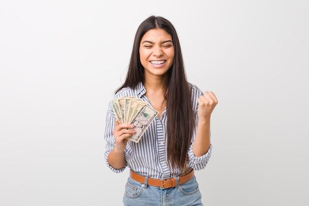 Giovane donna araba che tiene i dollari che incoraggiano spensierata ed eccitata. concetto di vittoria.