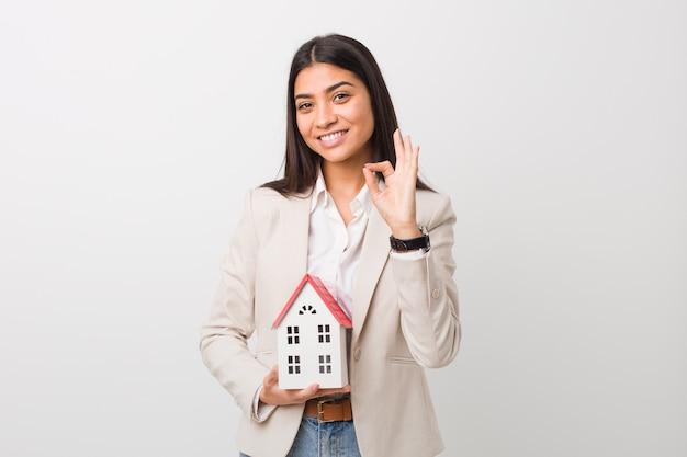 Giovane donna araba che tiene un'icona della casa allegro e fiducioso che mostra gesto giusto.