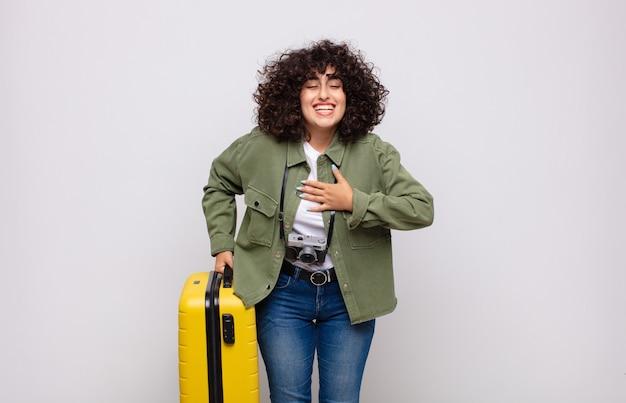 Giovane donna araba che ride ad alta voce a uno scherzo esilarante, sentendosi felice e allegra, divertendosi con il concetto di viaggio