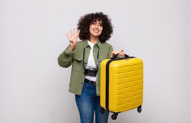 Giovane donna araba sorridente e guardando amichevole, mostrando il numero quattro o quarto con la mano in avanti, contando il concetto di viaggio