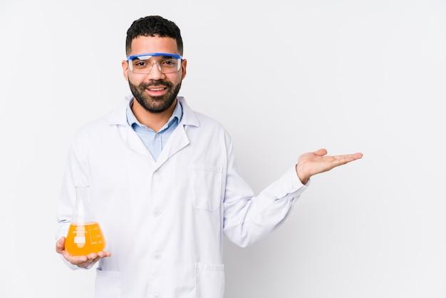 Giovane uomo chimico arabo isolato che mostra uno spazio di copia su una palma e che tiene un'altra mano sulla vita.