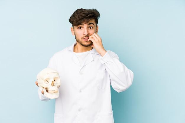 Giovane uomo medico arabo che tiene un cranio che morde le unghie, nervoso e molto ansioso.