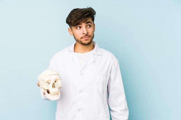 Il giovane medico arabo che tiene un teschio confuso, si sente dubbioso e insicuro.