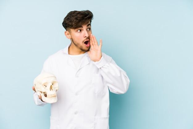 Il giovane uomo arabo di medico che tiene un cranio sta dicendo una notizia di frenata calda segreta e sta guardando da parte