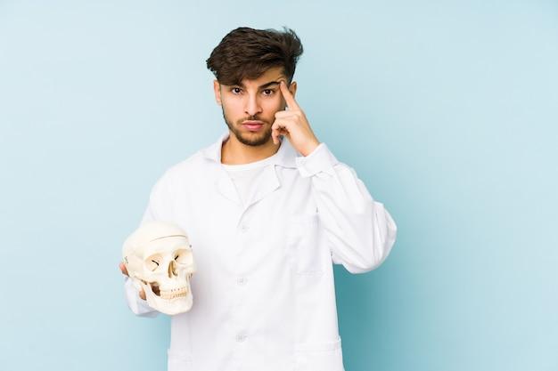 Uomo giovane medico arabo che tiene un tempio puntato teschio con il dito, pensando, concentrato su un compito
