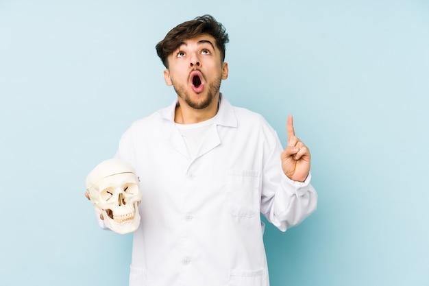Uomo giovane medico arabo che tiene un teschio rivolto verso l'alto con la bocca aperta.