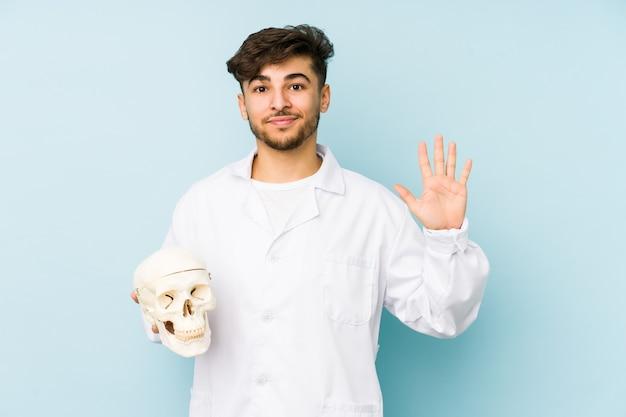 Uomo giovane medico arabo che tiene un teschio sorridente che mostra allegro numero cinque con le dita.