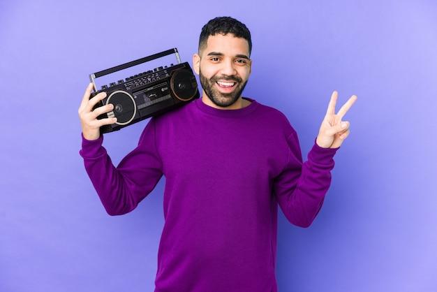 Giovane uomo arabo in possesso di una cassetta radio isolata giovane uomo arabo ascoltando musica gioiosa e spensierata che mostra un simbolo di pace con le dita.