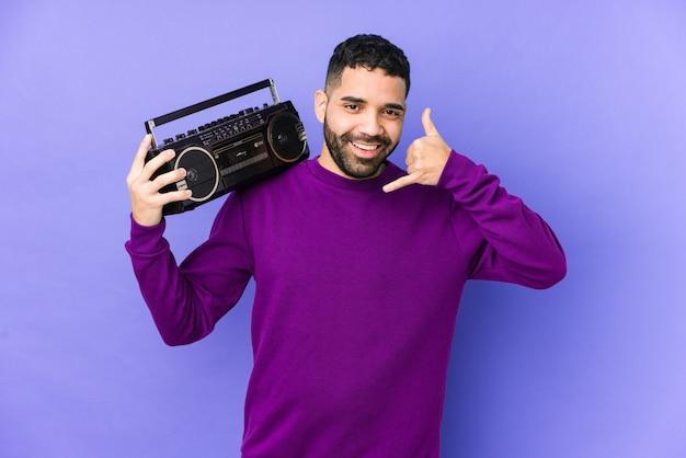 Giovane uomo arabo in possesso di una cassetta radio isolata musica d'ascolto giovane uomo arabo che mostra un gesto di chiamata di cellulare con le dita.