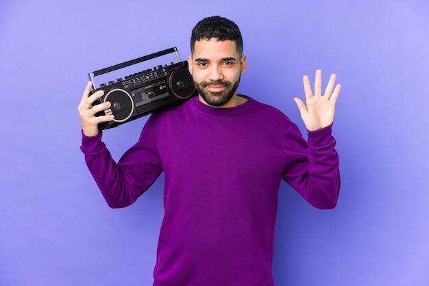 Giovane uomo arabo in possesso di una cassetta radio isolata giovane uomo arabo ascoltando musica sorridente allegro mostrando il numero cinque con le dita.
