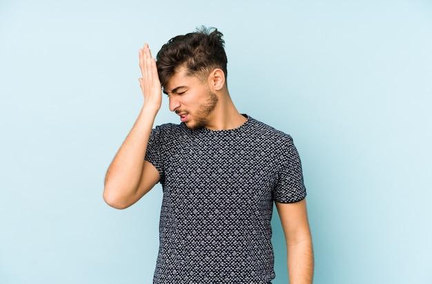 Giovane uomo arabo isolato su uno sfondo blu dimenticando qualcosa, schiaffeggiando la fronte con il palmo e chiudendo gli occhi.