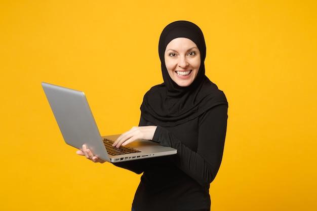 La giovane donna musulmana araba dell'impiegato in vestiti neri del hijab tiene e lavora il computer portatile del pc isolato sul ritratto giallo della parete. concetto di stile di vita religioso della gente. Foto Premium