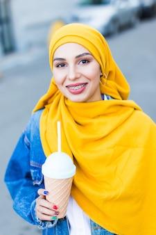 Giovane donna musulmana araba che gode del cocktail all'aperto.