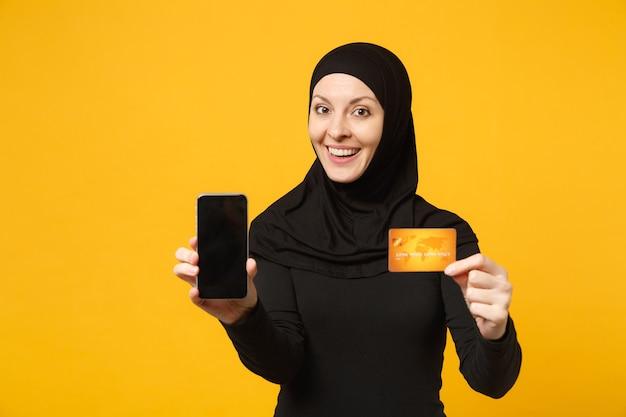 La giovane donna musulmana araba in abiti neri hijab tiene in mano il telefono cellulare, carta di credito isolata sul ritratto giallo della parete. concetto di stile di vita religioso della gente.