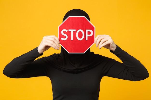 La giovane donna musulmana araba in vestiti neri di hijab tiene in mano il segno rosso con il titolo di arresto isolato sul ritratto giallo della parete. concetto di stile di vita religioso della gente. .