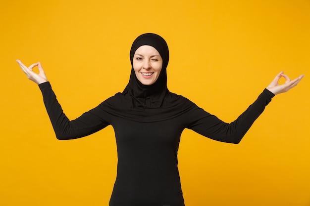 La giovane donna musulmana araba in vestiti neri di hijab si tiene per mano nel gesto di yoga, si rilassa meditando isolato sul ritratto giallo della parete. concetto di stile di vita religioso della gente.