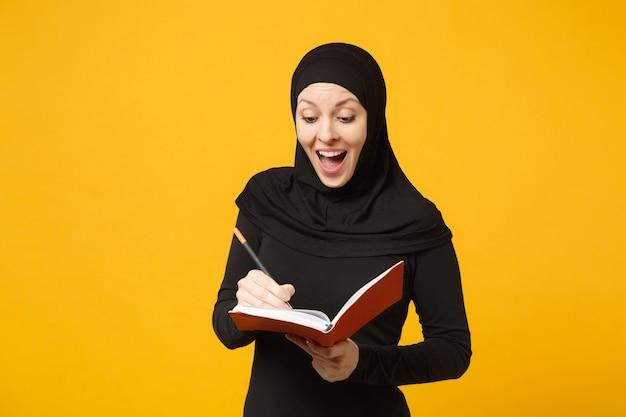 La giovane donna musulmana araba in abiti neri hijab tiene il taccuino, scrive, si prepara all'esame isolato sul ritratto giallo della parete. concetto di stile di vita religioso della gente. .