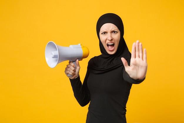 La giovane donna musulmana araba in vestiti neri del hijab tiene in mano il megafono di discorso pubblico dell'altoparlante isolato sul ritratto giallo della parete. concetto di stile di vita religioso della gente.