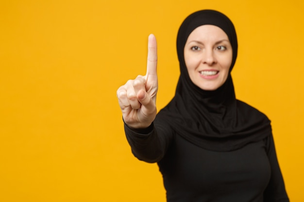 La giovane donna musulmana araba in abiti neri hijab tocca qualcosa come premere clic sul pulsante isolato sul ritratto giallo della parete. concetto di stile di vita religioso della gente.