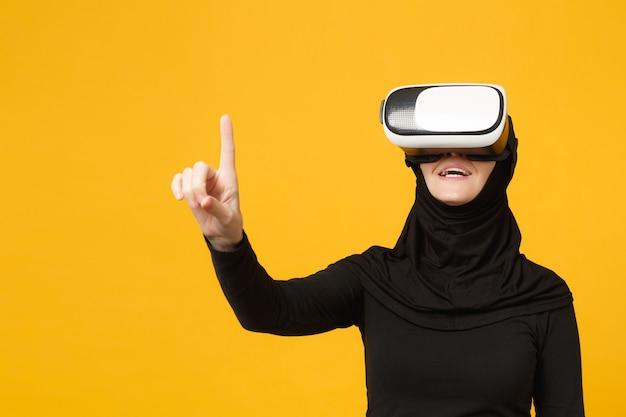 Giovane donna musulmana araba in abiti neri hijab guardando in cuffia della realtà virtuale vr isolata sul ritratto giallo della parete. concetto di stile di vita religioso della gente.