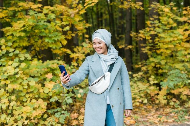 Giovane donna musulmana araba in abiti hijab facendo selfie girato sul telefono cellulare nel parco. concetto di stile di vita religioso della gente. copia spazio.