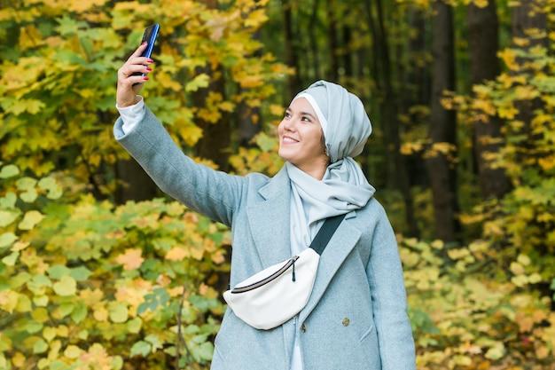 Giovane donna musulmana araba in abiti hijab che fa selfie sparato sul telefono cellulare nel parco persone