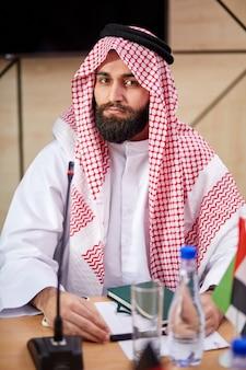 Giovane sceicco arabo uomo che indossa abiti tradizionali emirati si siede alla scrivania sulla riunione di lavoro, musulmano di affari arabo saudita maschio che esamina seriamente la macchina fotografica