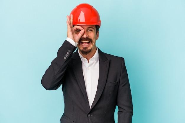 Il giovane uomo caucasico dell'architetto isolato su fondo blu ha eccitato mantenendo il gesto giusto sull'occhio.