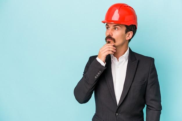 Giovane uomo caucasico architetto isolato su sfondo blu guardando lateralmente con espressione dubbiosa e scettica.