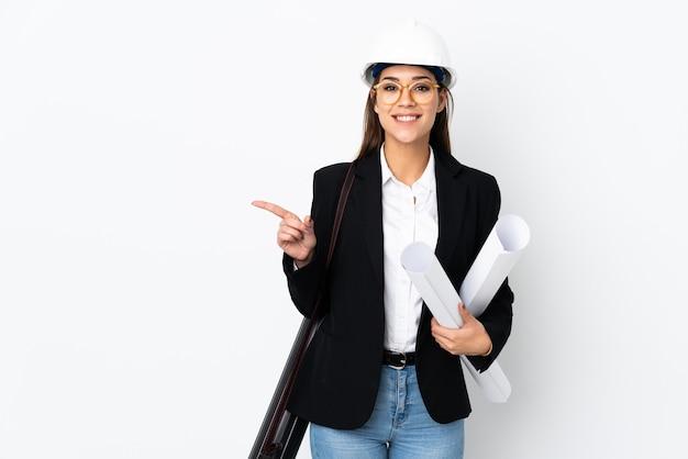 Giovane donna caucasica dell'architetto con il casco e che tiene i modelli e