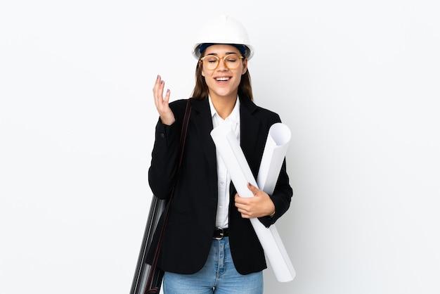 Giovane donna indoeuropea architetto con casco e tenendo i modelli