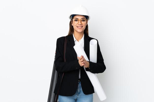 Donna caucasica del giovane architetto con il casco e le cianografie della holding