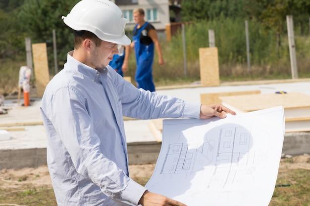 Giovane architetto che controlla un disegno strutturale o un progetto mentre si trova sul cantiere di una nuova casa