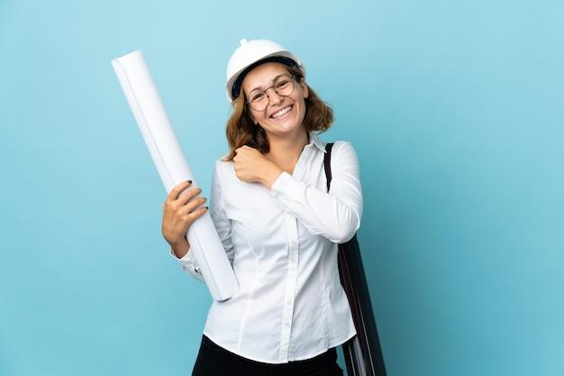Giovane donna georgiana dell'architetto con il casco e che tiene i modelli sopra fondo isolato che celebra una vittoria