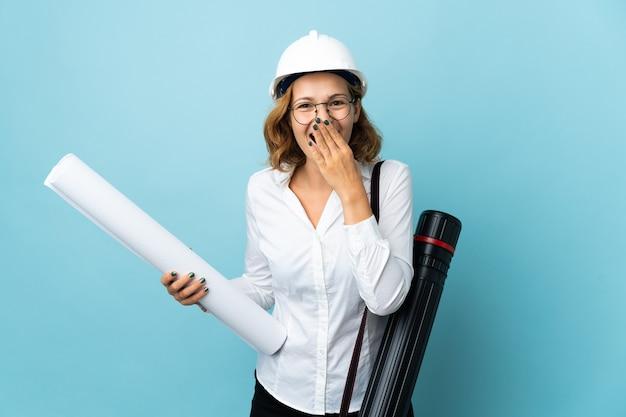 Giovane donna georgiana dell'architetto con il casco e che tiene i modelli sopra fondo isolato felice e sorridente che copre la bocca con la mano