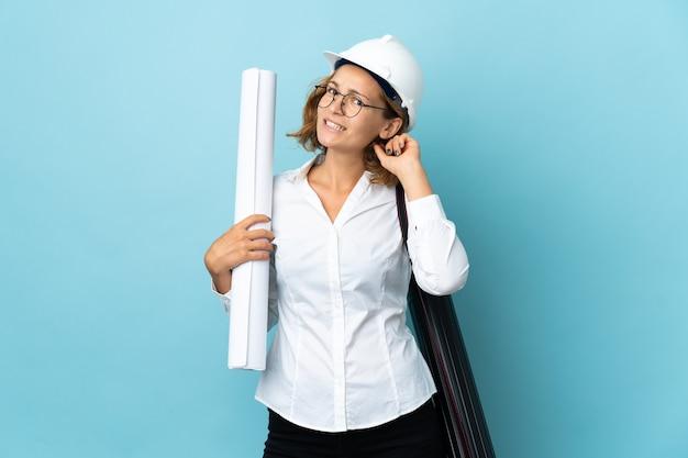 Giovane donna georgiana architetto con casco e azienda blueprint su sfondo isolato avendo dubbi